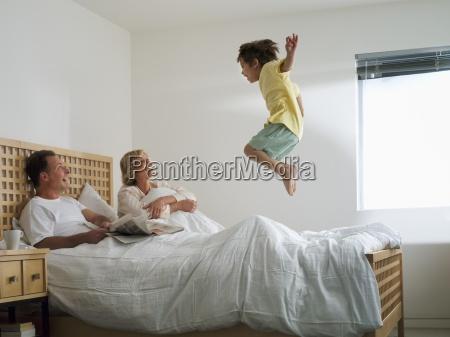 rodzice lezacy w podwojnym lozku w