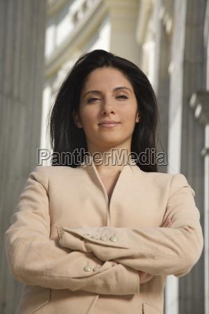 cross armed businesswoman looking