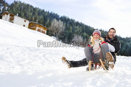 young couple on sled in snow