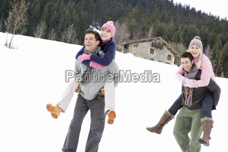 two young couples smiling in snow