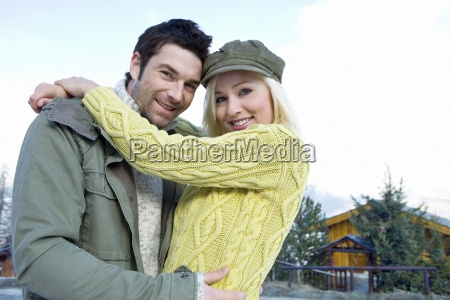 young couple embracing outdoors in snow