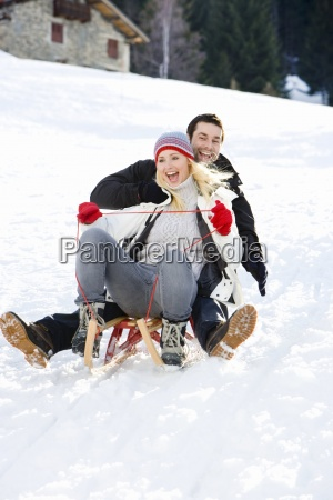 young couple riding sled down snow