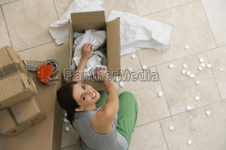 kobieta siedzi na podlodze pudelko z