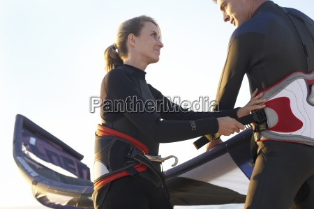 young couple in wetsuits preparing to