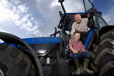 portrait of smiling farmer and grandson