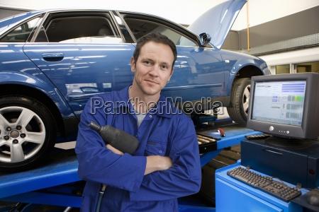 mechanik w warsztacie auto obok komputera