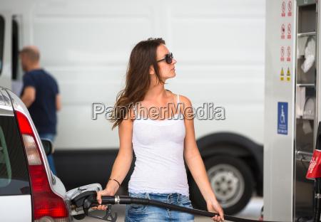 atrakcyjna mloda kobieta tankowania swojego samochodu