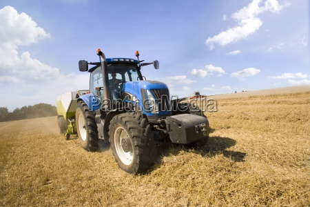 tractor and straw baler in sunny