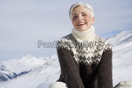 happy starsza kobieta siedzi w gorach