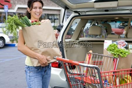 kobieta zaladunku samochodu z toreb spozywczych
