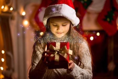cute girl patrzac wewnatrz swiecace christmas