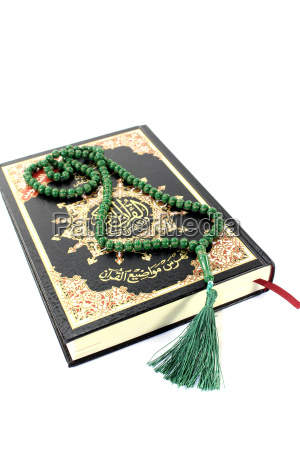 the koran with a green rosary