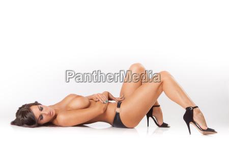 atrakcyjna brunetka dziewczyna lezy na bialej