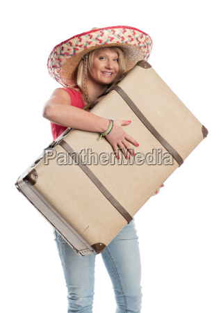 woman with sombrero carrying a suitcase