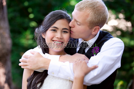 caucasian groom lovingly kissing his biracial