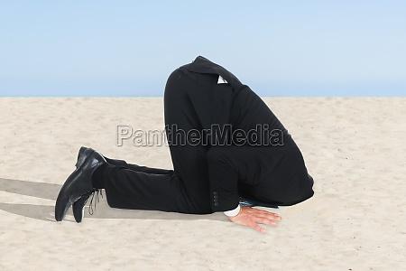 biznesmen ukrywanie sand glowa