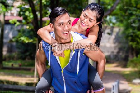 asian mezczyzna przewozacy swoja dziewczyne piggyback