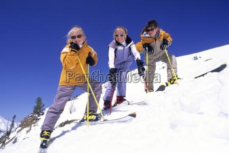 trzy usmiechniete dzieci na stokach narciarskich