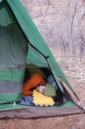 mlody czlowiek spi w otwartym namiocie
