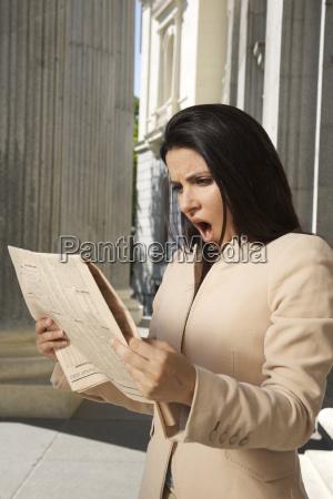 shocked businesswoman reading newspaper
