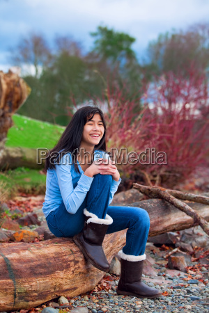 young teen girl sitting on log