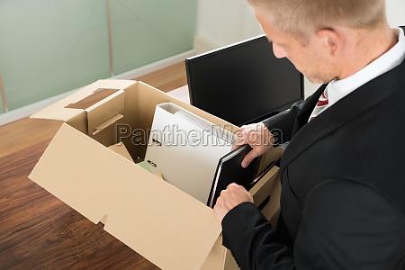 biznesmen pakowania plikow w kartonik
