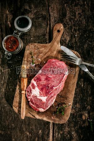 surowy rib eye steak na drewnianej