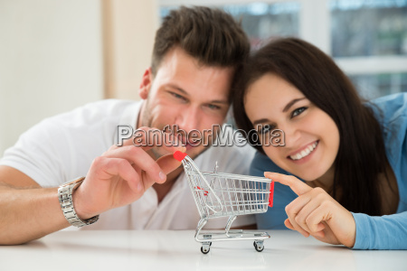 smiling couple with miniature shopping cart