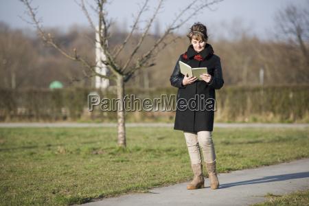 kobieta spaceru i boczne czytanie