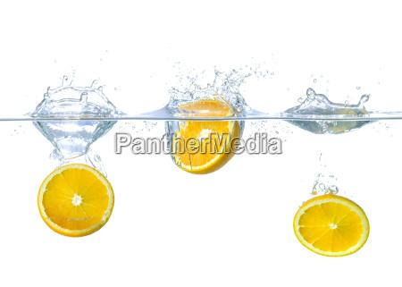 pomarancze wpadaja do wody z rozpryskami