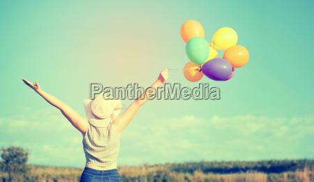 zdjecie mlodej kobiety z kolorowych balonow