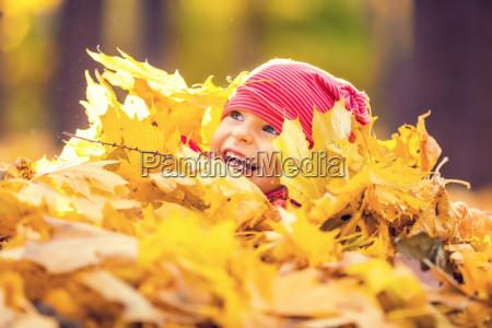 mala dziewczynka bawi sie jesiennymi liscmi