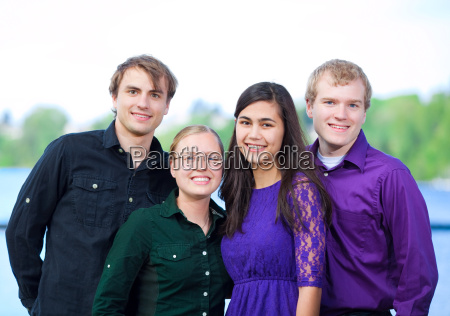 four young multiethnic friends standing