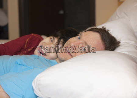 father sleeping in bed with disabled