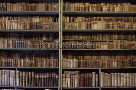 historyczne stare ksiazki w bibliotecedrewniany regal