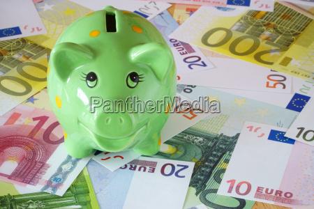 zielona swinka i banknoty euro na
