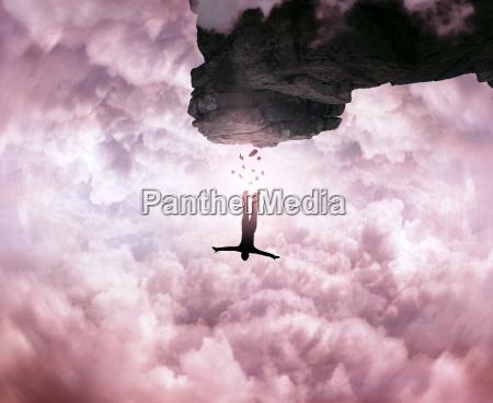 sylwetka mlodego czlowieka skaczacego z szczytu