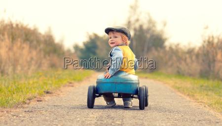 smiejacy sie chlopiec z pedalowym samochodem