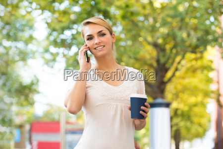 woman using mobile phone while holding