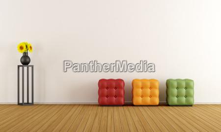 minimalistyczny bialy pokoj kolorowy pufy sciana