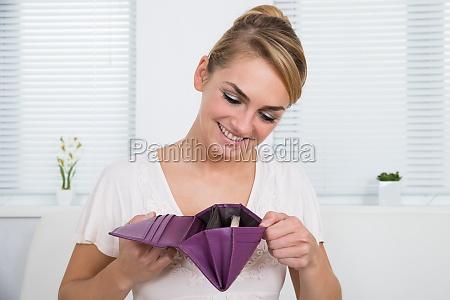 kobieta patrzac na pieniadze w torebce