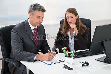 biznesmen pisanie na schowku z asystentem