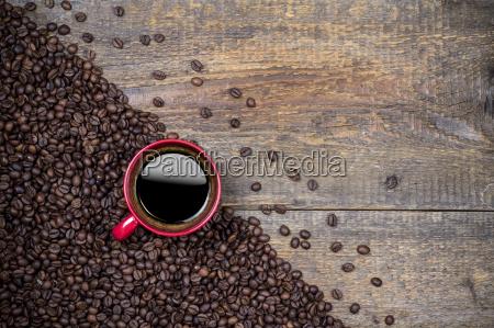ziarna kawy i czerwona filizanka kawy