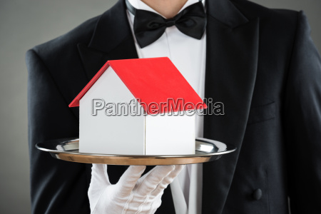 midsection of waiter holding house model