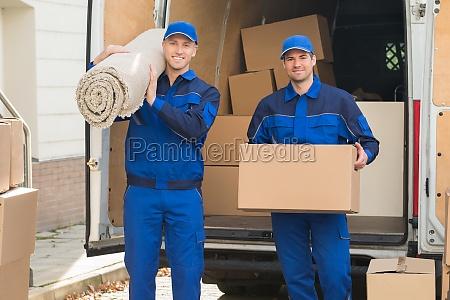 szczesliwa dostawa mezczyzn przewozacych kartonowe pudelko