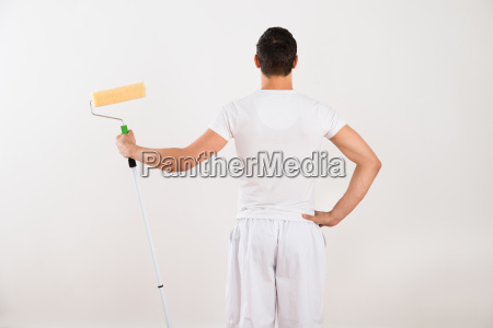 rear view of man holding paint