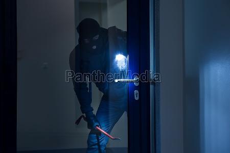 zlodziej z latarka probuje zlamac drzwi