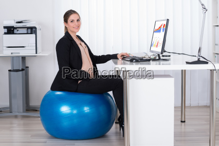 pregnant businesswoman sitting on fitness ball
