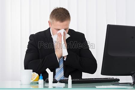 sick biznesmen wieje nos