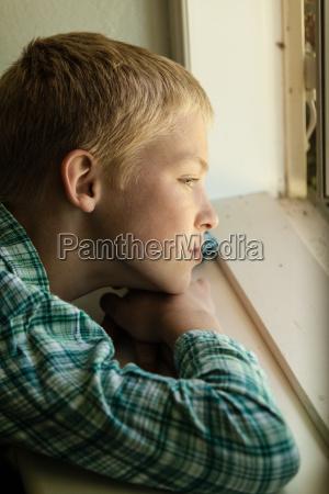 dziecko ze smutnym wyrazem siedzacym przy